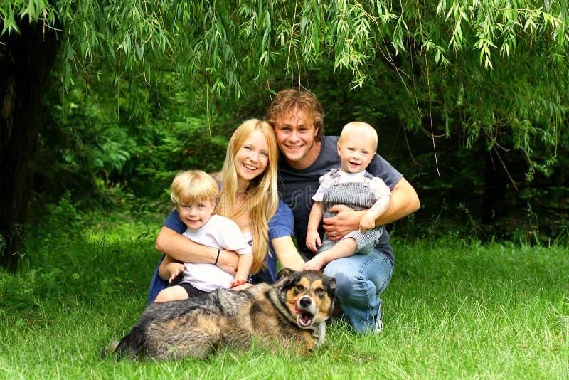 Счастливая семья сидя под деревом вербы стоковые изображения