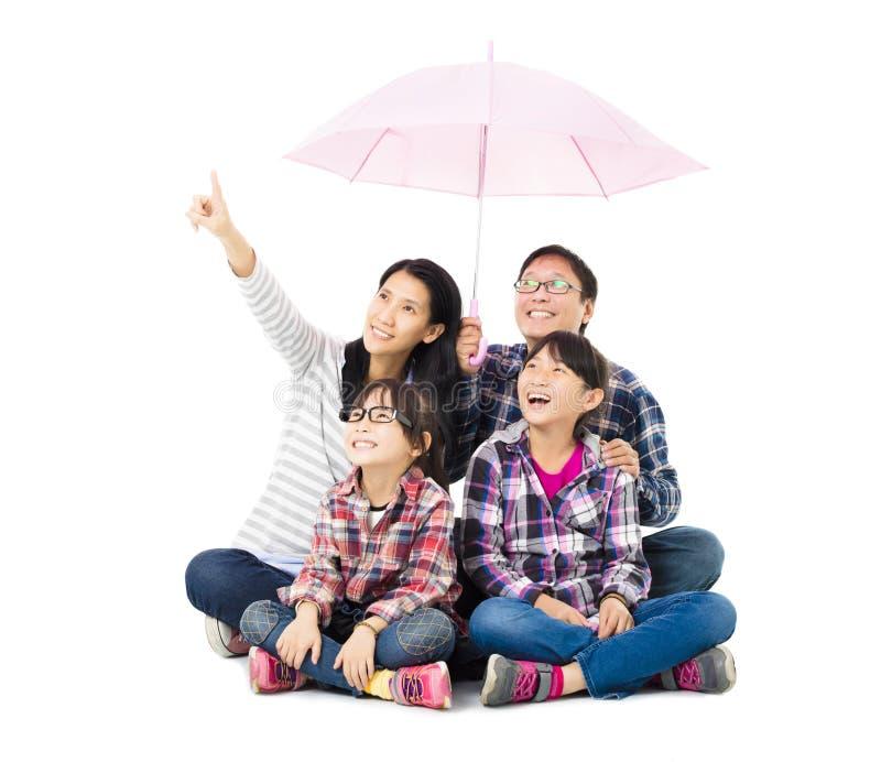 Счастливая семья сидя под зонтиком стоковое фото rf