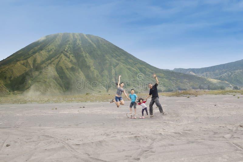 Счастливая семья скачет на вулканическую пустыню 1 стоковое изображение