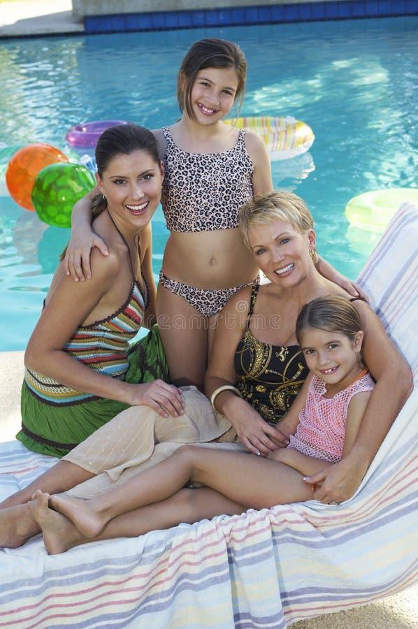 Счастливая семья совместно на Poolside стоковое изображение