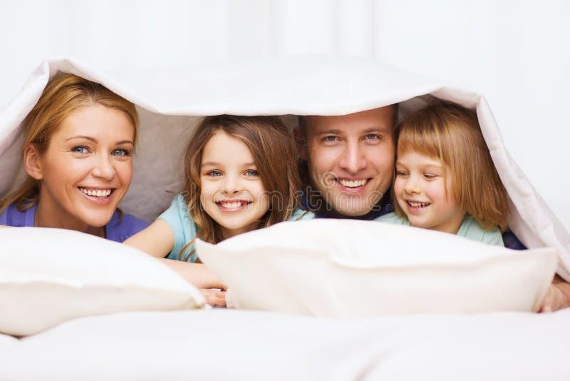 Счастливая семья с 2 детьми под одеялом дома стоковые изображения