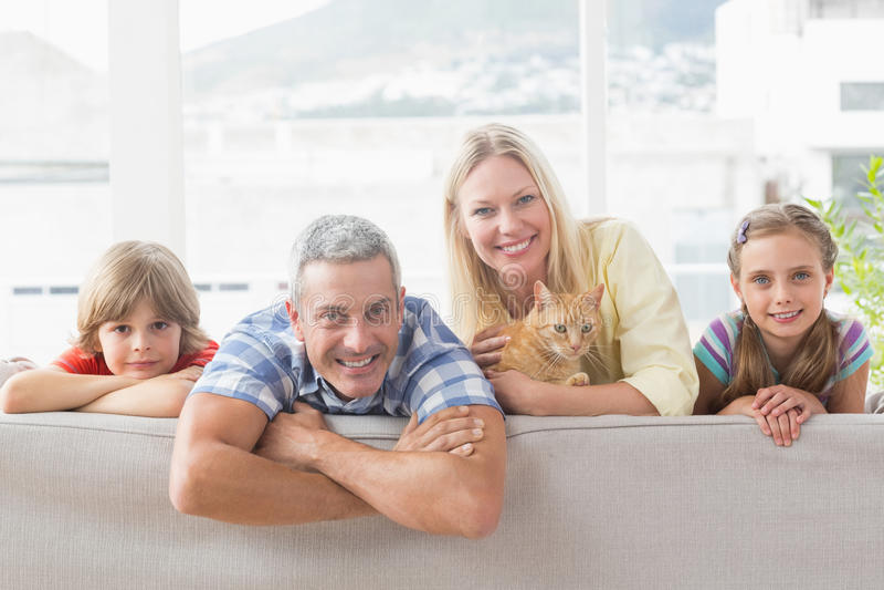 Счастливая семья с котом на софе дома стоковые фото