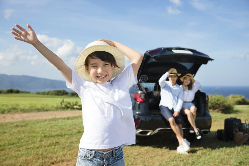 Счастливая семья с перемещением маленькой девочки автомобилем стоковая фотография rf