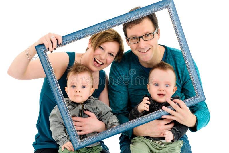 Счастливая семья с принятыми близнецами смеется над Изолировано на белизне стоковое фото rf