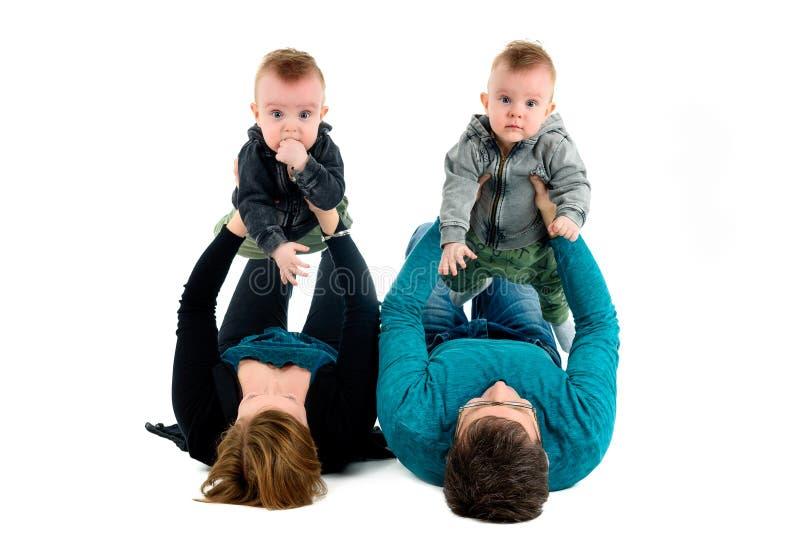 Счастливая семья с принятыми близнецами смеется над Изолировано на белизне стоковые фотографии rf