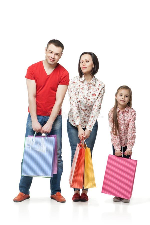 Счастливая семья с хозяйственными сумками стоковые изображения