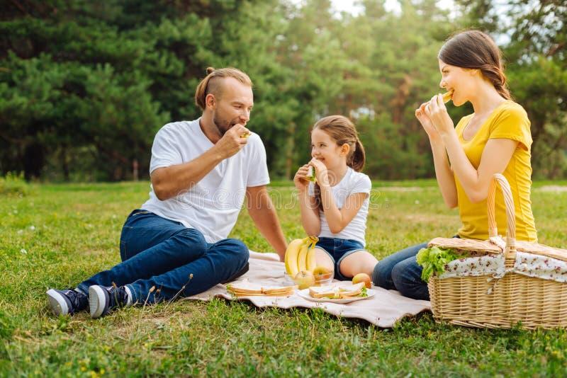 Счастливая симпатичная семья есть сандвичи на пикнике стоковая фотография