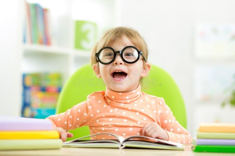 Счастливая смешная девушка ребенка в стеклах читая книгу стоковая фотография
