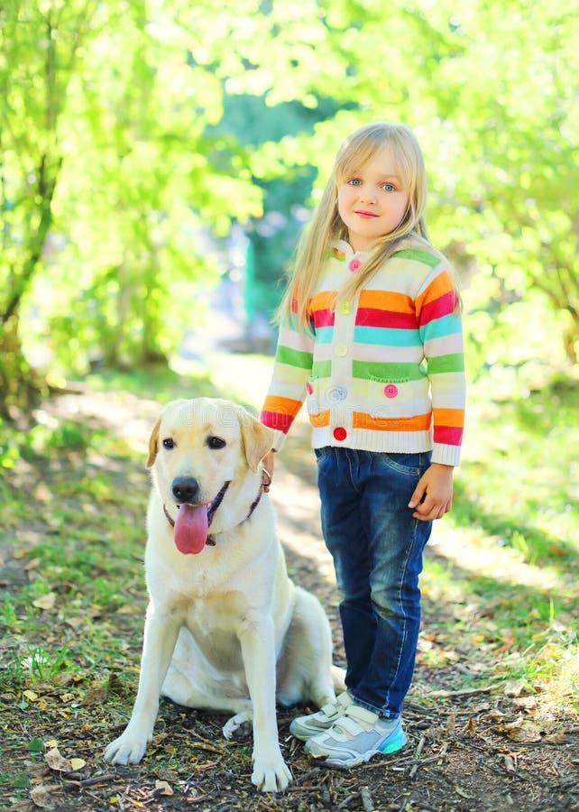 Счастливая собака retriever labrador и маленький ребенок в лете стоковая фотография