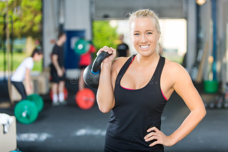 Счастливая спортсменка поднимая Kettlebell стоковая фотография rf