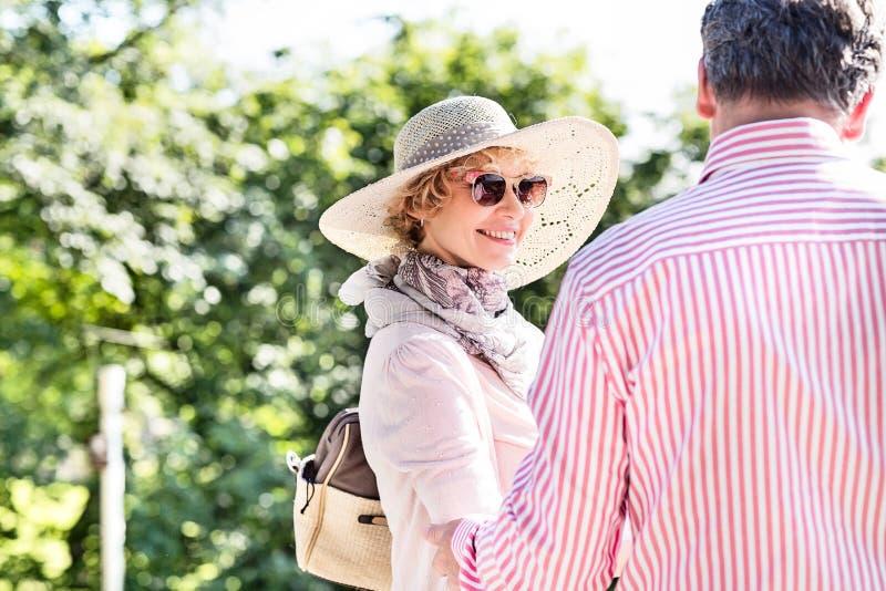 Счастливая средн-постаретая женщина с человеком в парке стоковая фотография rf