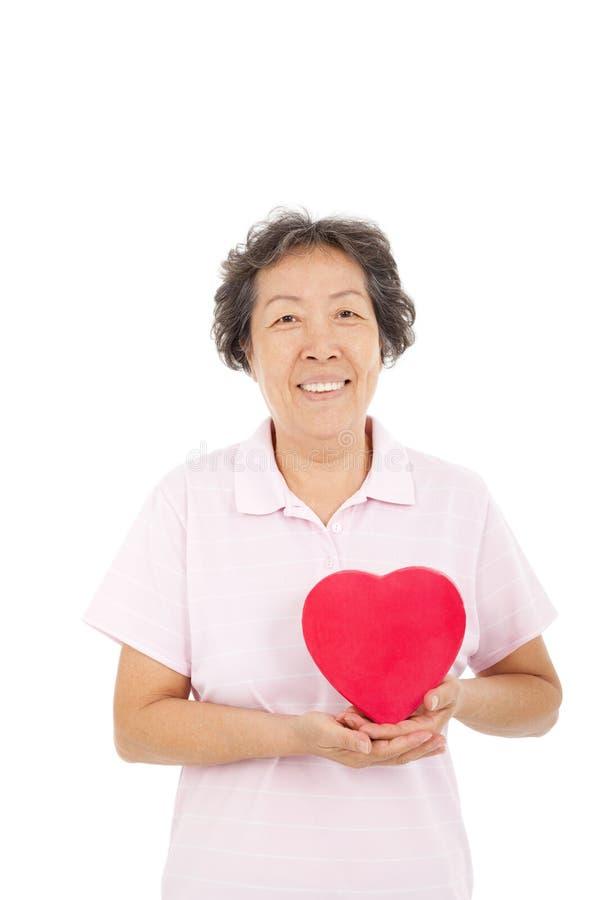Счастливая старшая женщина с красным сердцем стоковые изображения