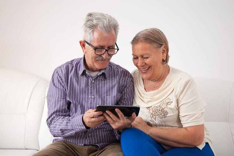 Счастливая старшая пара используя цифровую таблетку стоковая фотография rf