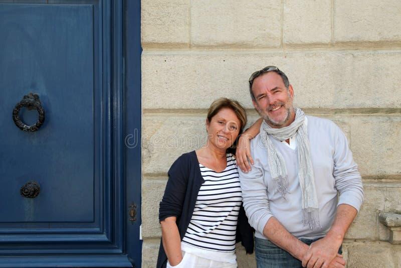 Счастливая старшая склонность пар на стене здания города стоковые фотографии rf