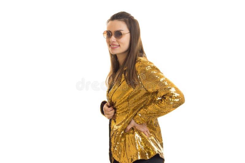 Счастливая стильная женщина в золотых куртке и солнечных очках стоковые изображения rf