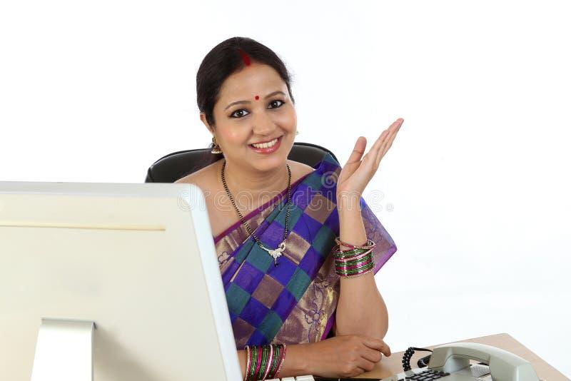 Счастливая традиционная индийская бизнес-леди на столе офиса стоковые фотографии rf