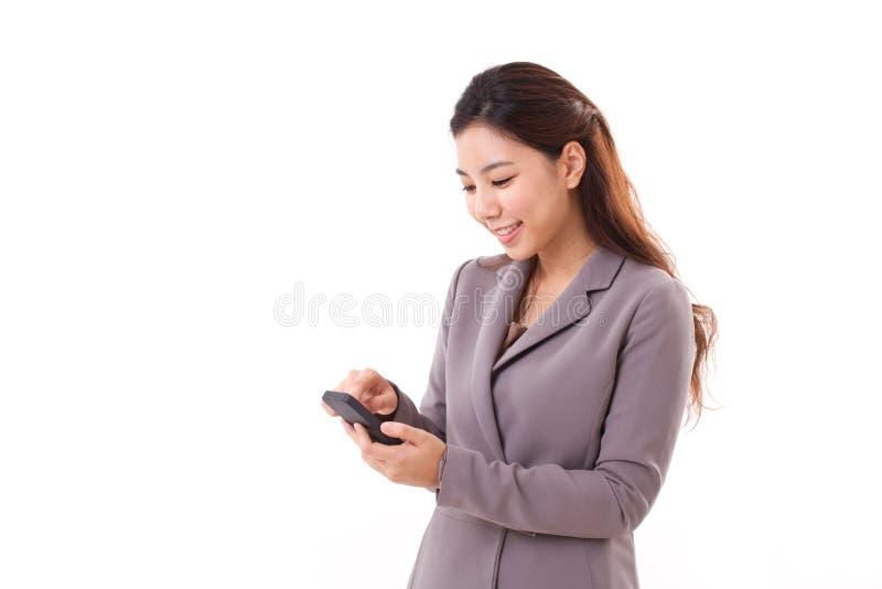 Счастливая, усмехаясь бизнес-леди отправляя СМС, через ее smartphone стоковое фото rf