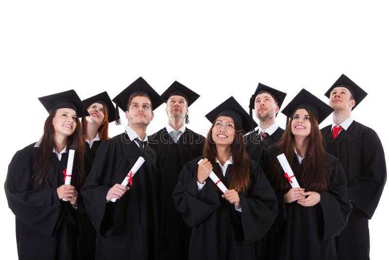 Счастливая усмехаясь группа в составе многонациональные студент-выпускники стоковое фото rf