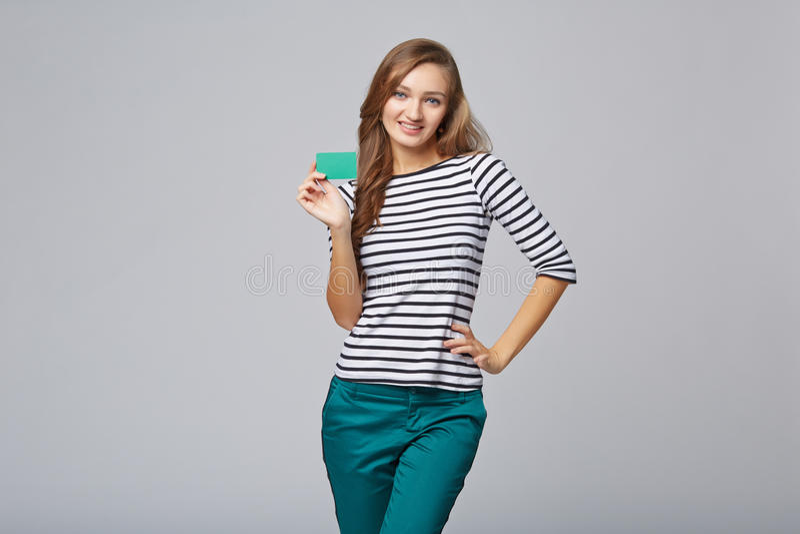 Счастливая усмехаясь девушка в вскользь одежде, показывая кредитную карточку кредита без обеспечения стоковое фото