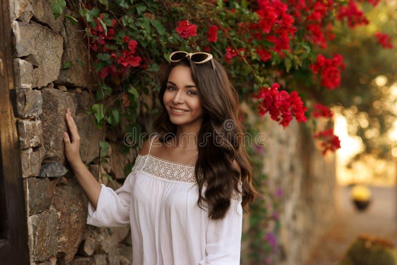 Счастливая усмехаясь девушка против цветков стоковые фото