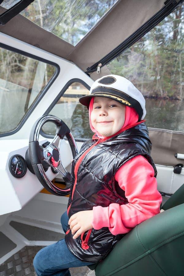 Счастливая усмехаясь девушка управляя моторкой как капитан на палубе стоковое фото rf