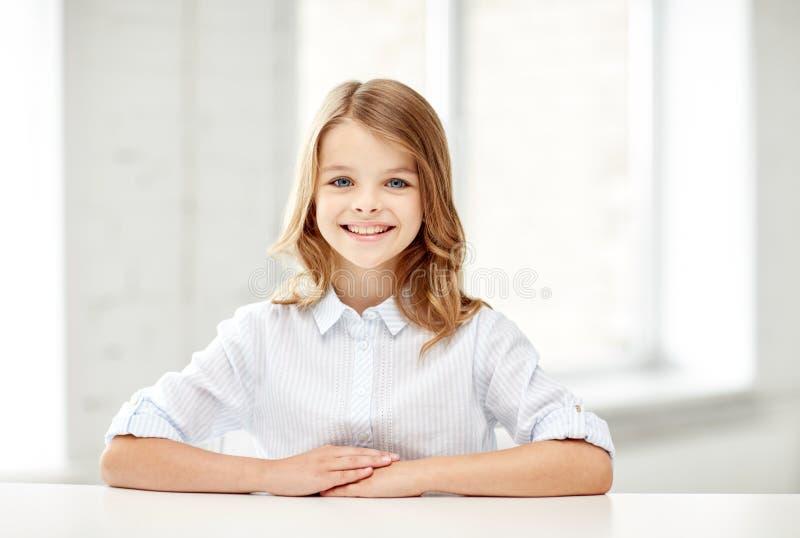 Счастливая усмехаясь девушка школы сидя на таблице стоковые фотографии rf