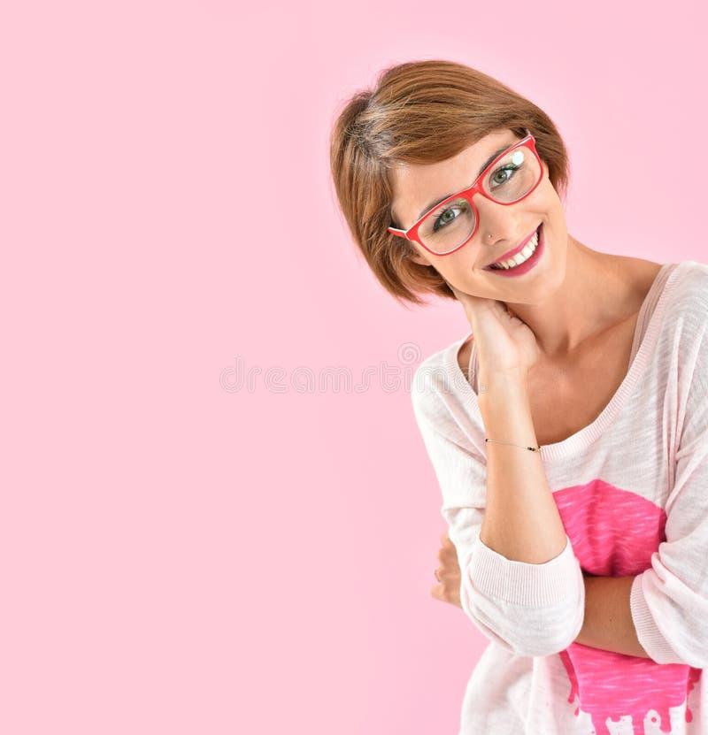 Счастливая усмехаясь женщина нося красные eyeglasses стоковые изображения