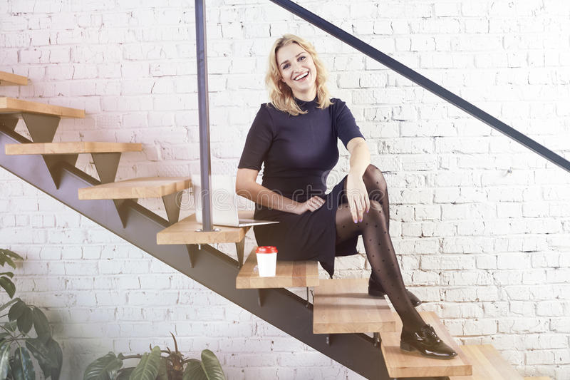 Счастливая усмехаясь коммерсантка сидя на лестницах в современном офисе, работая на компьтер-книжке и имея кофе, дневной свет сол стоковые изображения rf