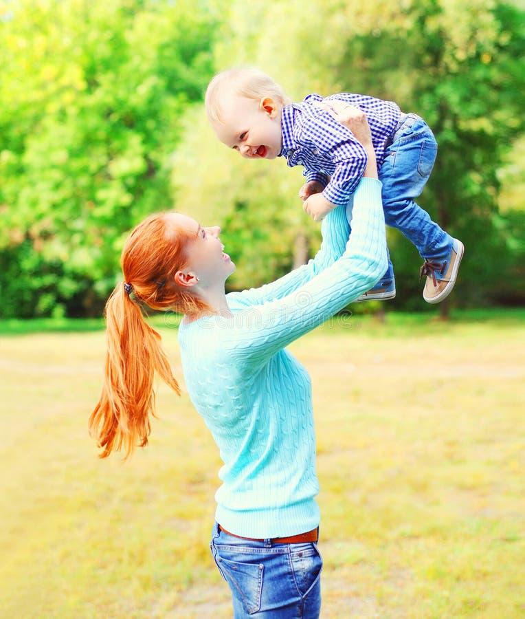 Счастливая усмехаясь мать с ребенком сына имеет потеху совместно outdoors на лете стоковые фотографии rf