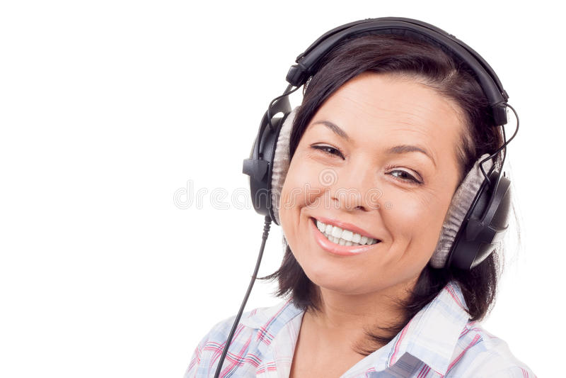 Счастливая усмехаясь музыка красивой молодой женщины слушая с Headpho стоковые фотографии rf