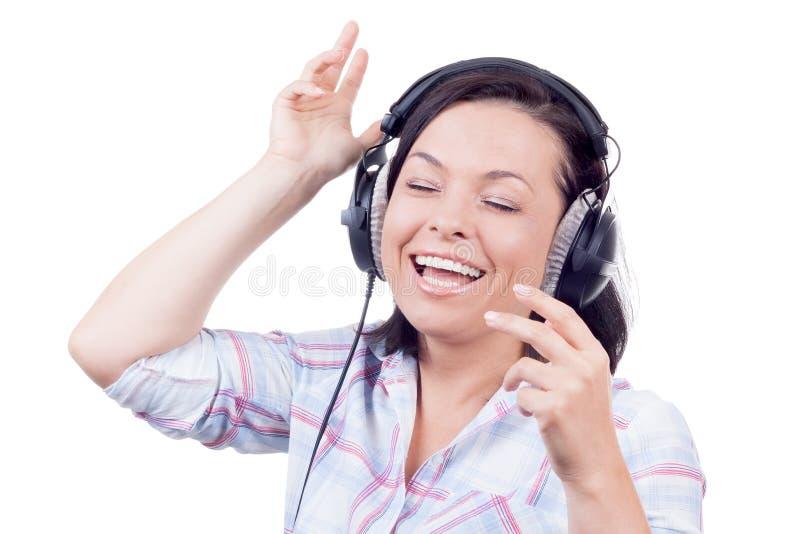 Счастливая усмехаясь музыка красивой молодой женщины слушая с Headpho стоковое изображение rf