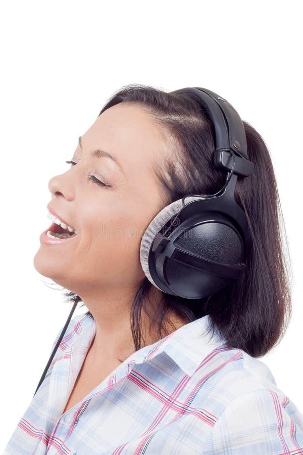 Счастливая усмехаясь музыка красивой молодой женщины слушая с Headpho стоковые фото