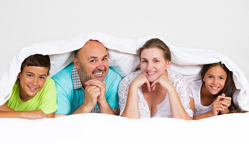 Счастливая, усмехаясь семья под одеялом стоковое изображение rf
