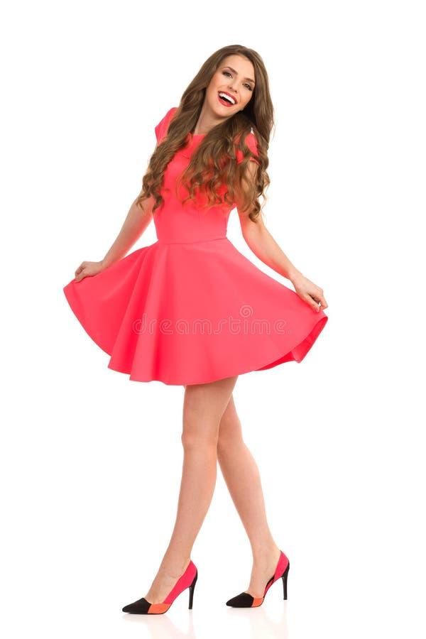 Счастливая фотомодель идя в розовое мини платье стоковая фотография rf