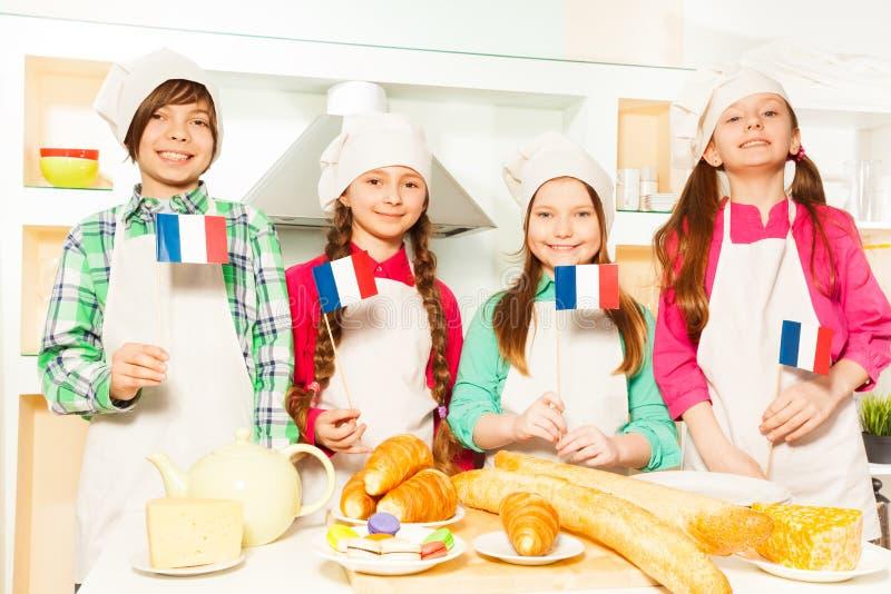 Счастливая французская команда 4 молодых хлебопеков стоковое изображение