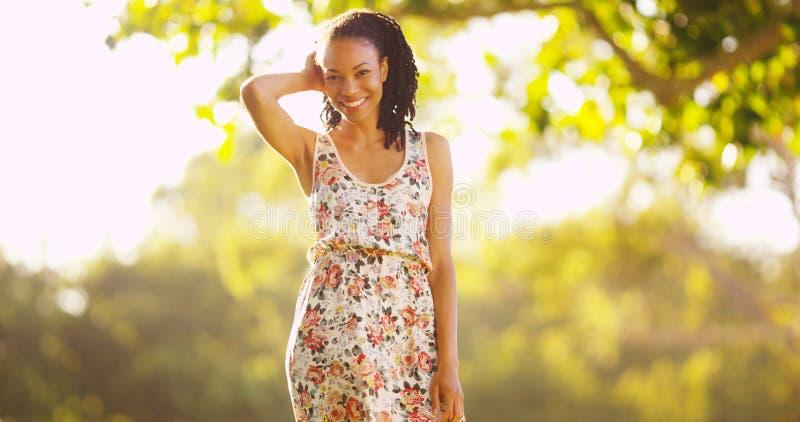 Счастливая чернокожая женщина стоя на траве стоковая фотография rf