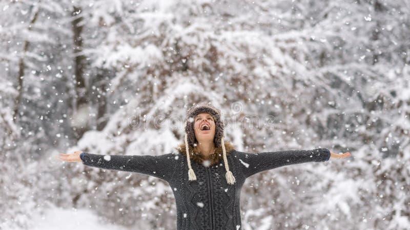 Счастливая vivacious женщина празднуя снег стоковые изображения