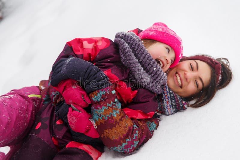 Счастливое брюнет, дочь на снеге стоковые изображения rf