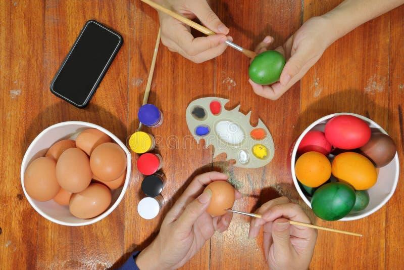 Счастливое время семьи членов красит красочные яичка с кистью для подготавливает день пасхи стоковое фото