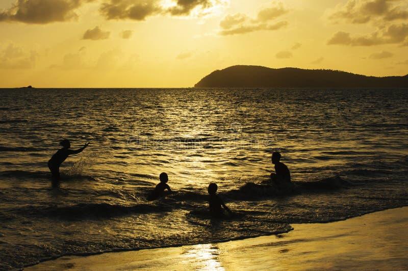 Счастливое заплывание семьи на заходе солнца стоковая фотография rf