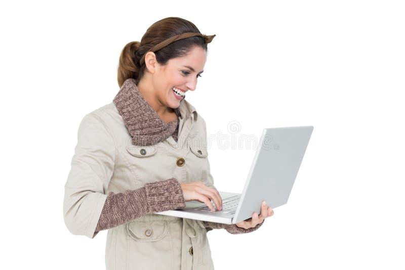 Счастливое милое брюнет в моде зимы используя компьтер-книжку стоковое изображение