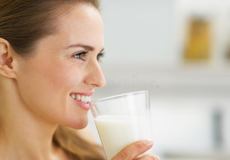 Счастливое молодое питьевое молоко домохозяйки стоковые фотографии rf