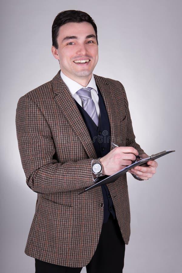 Счастливое молодое сочинительство бизнесмена что-то на доске сзажимом для бумаги над gre стоковое изображение rf