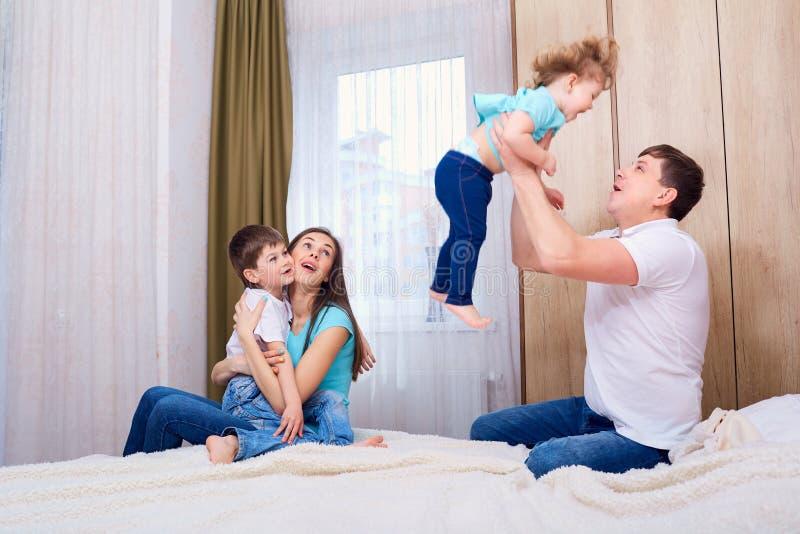 Счастливое объятие отца его дочь при мать улыбки сидя с сыном стоковая фотография rf