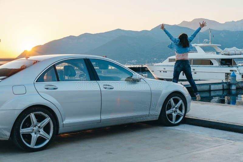 Счастливое перемещение женщины автомобилем к морю и скакать на заход солнца Summ стоковые изображения rf