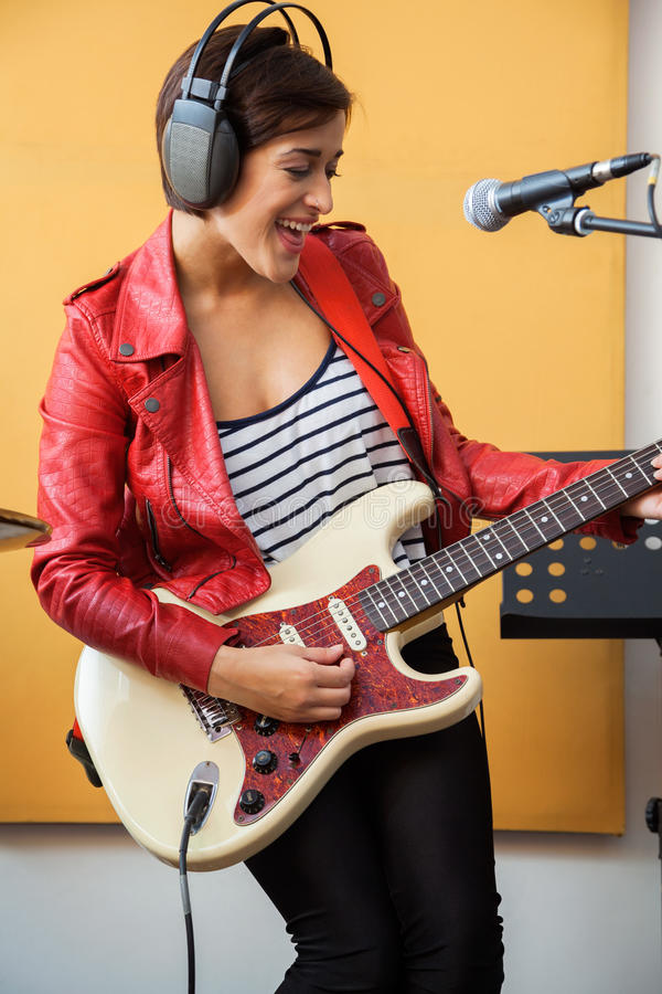 Счастливое подписывающее лицо играя гитару в студии звукозаписи стоковые изображения rf