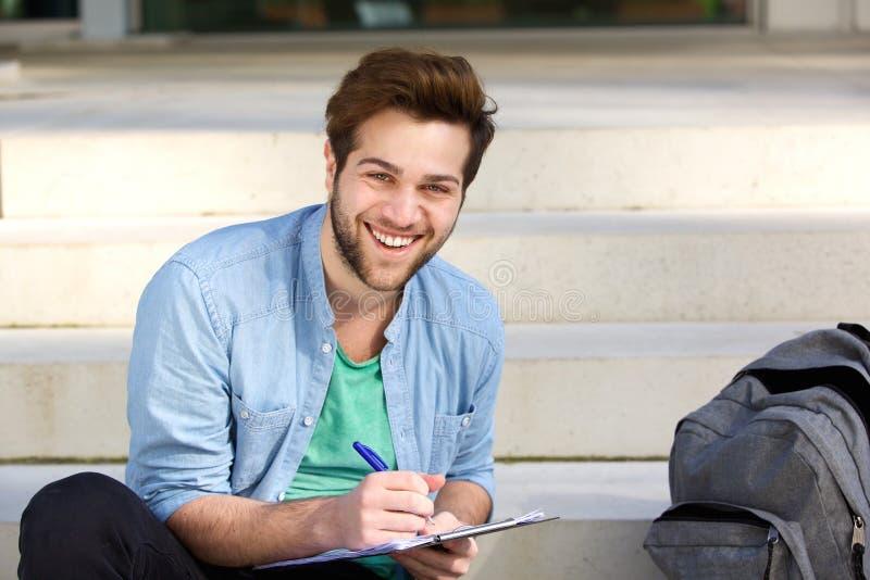 Счастливое сочинительство студента колледжа на блокноте снаружи стоковая фотография