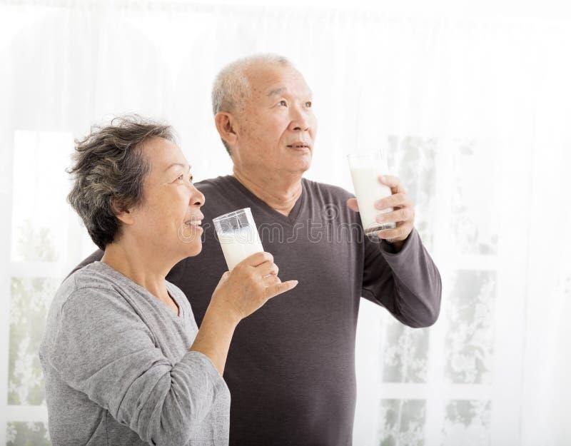 Счастливое старшее питьевое молоко пар стоковое изображение rf