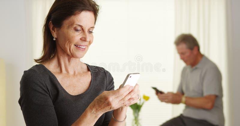 счастливое старшее smartphone используя женщину стоковое фото