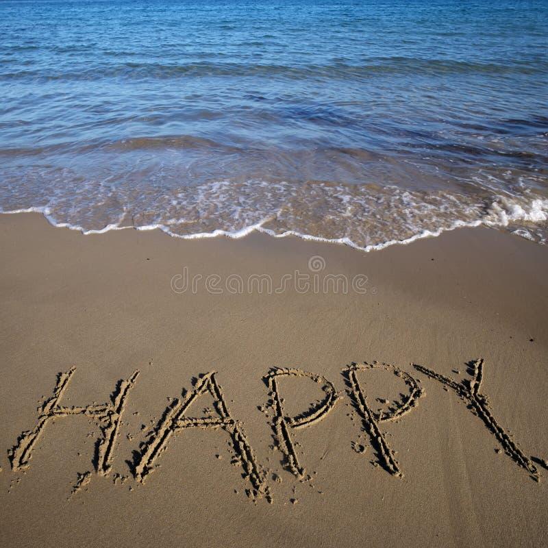 Счастливое слова написанное на песке стоковое фото rf